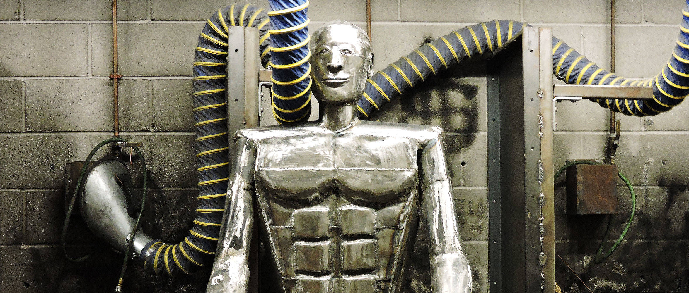 A metal sculpture of a man representing student information for Apex Technical School