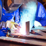 A team of two welders work together in a hands-on shop class to gain experiential learning skills for the workforce