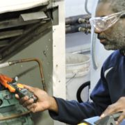 An Apex student works on A/C refrigeration repairs while learning a trade