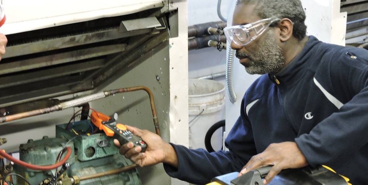 an apex student works on ac refrigeration repairs while learning a trade