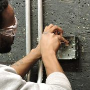 An Apex student uses electrical tools to install a light fixture