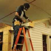 An Apex student stands on a ladder and uses wood working tools