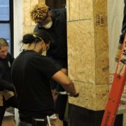 Individuals in construction career path take measurements for door installation