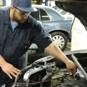 Student checks engine in automotive repair training class
