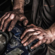 An auto repair student with greasy hands trains for a skilled trade job