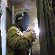 A welding student wears protective gear and learns to use welding tools