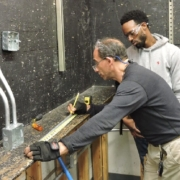 An electrical instructor shows a student how to take electrical measurements in shop class