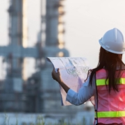 Woman with a white hard hat holds a blueprint on a construction jobsite