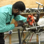 An Apex student wearing a green shirt learns to repair a plumbing fixture in a plumber training class