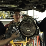 Hands-on auto repair students stand under a car and learn to replace parts