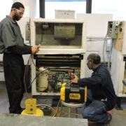An air conditioning and refrigeration student learns hands-on skills from an instructor