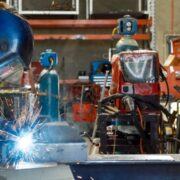 A student wearing protective gear practices MIG welding