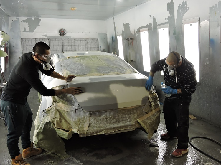 Apex auto body students painting a car