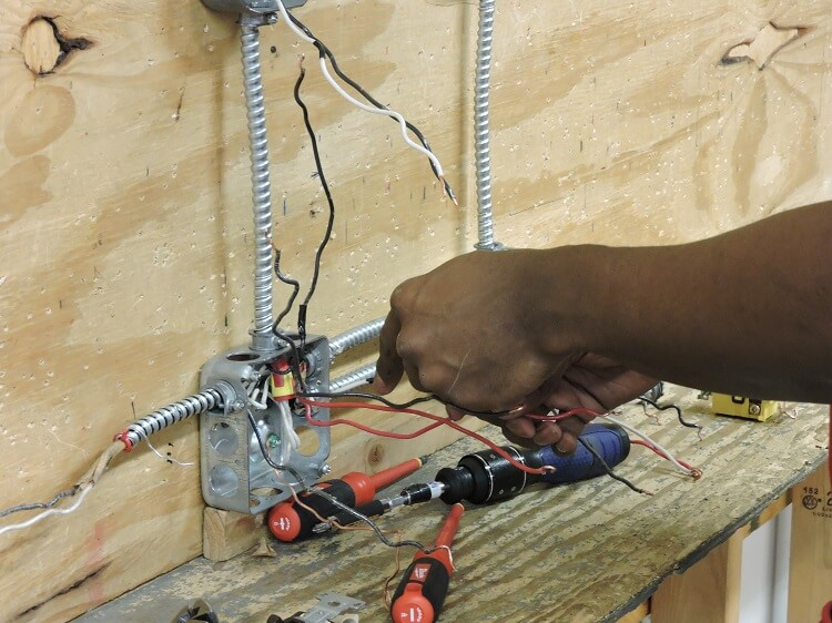 Apex student using tools for an electrical task