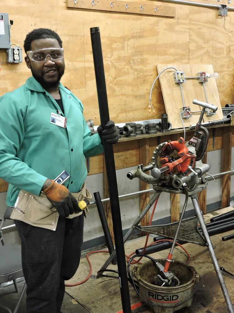 Apex plumbing student with pipe