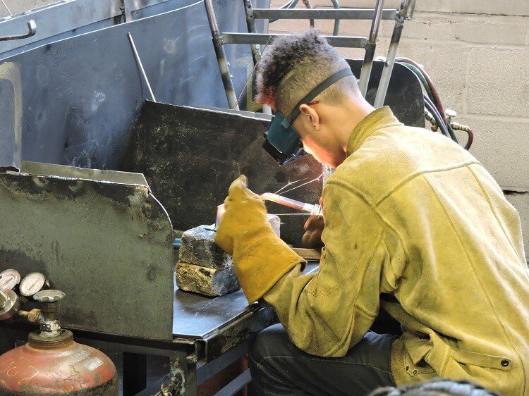 Apex welding student with tools