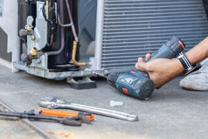 Air conditioning repair technician uses a drill to make HVAC repairs