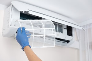 HVAC technician replaces an air conditioning filter