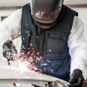 A welder repairs a damaged car with automotive MIG welding