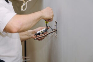 An electrician helps install a home electrical outlet