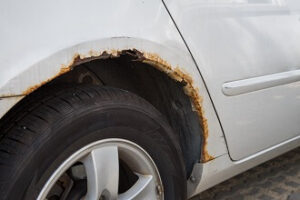 A silver car with rust spots above the tire, a common problem with older cars