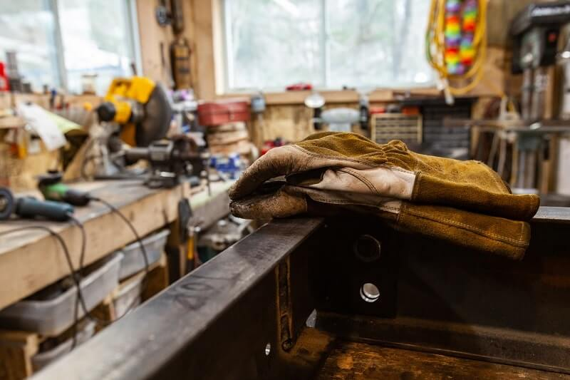 A pair of welder's protective hand gloves on a workbench