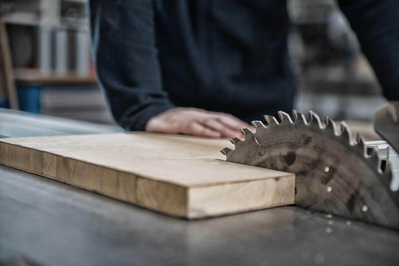 A construction trade school student learns how to use a table saw