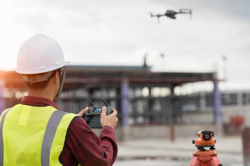 A construction worker flies a drone on a worksite