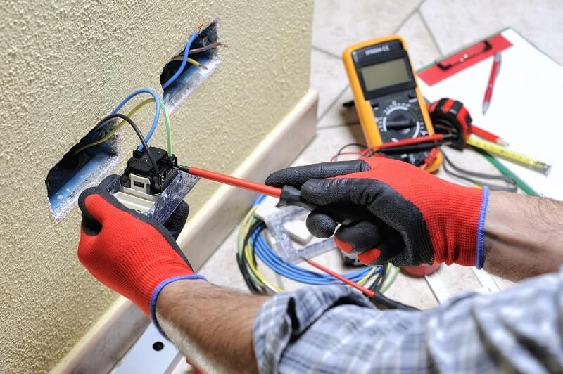 An electrician repairs home electrical wiring behind a light switch