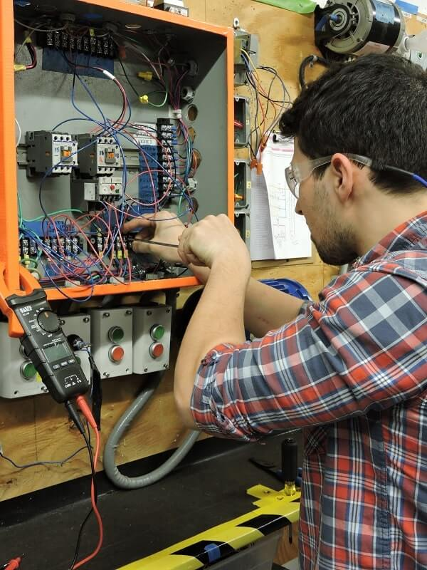 An Apex student in the Electrical & Advanced Electrical program learns to maintain a fuse box