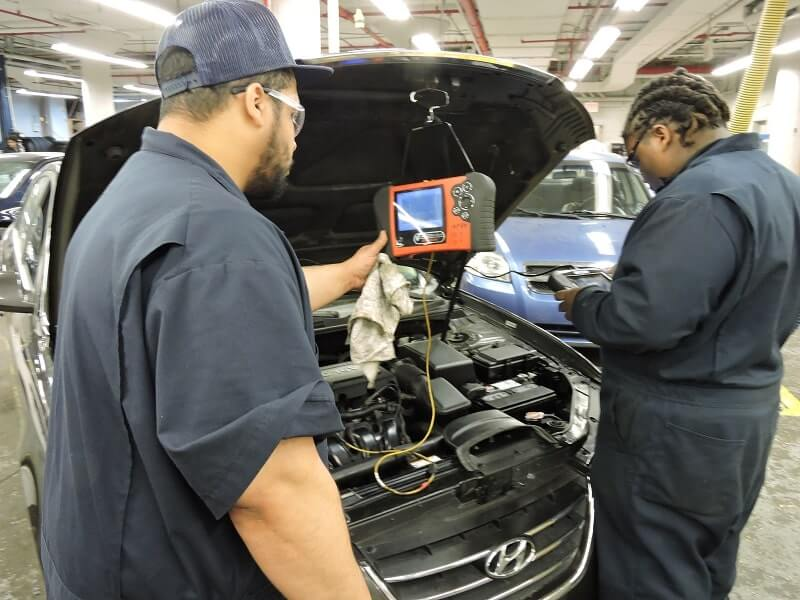 Two Apex students in the Automotive Service & Repair program learn to perform maintenance checks on a car