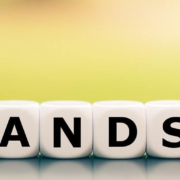 """A person using six dice pieces with letters to spell out the word """"hands on"""""""