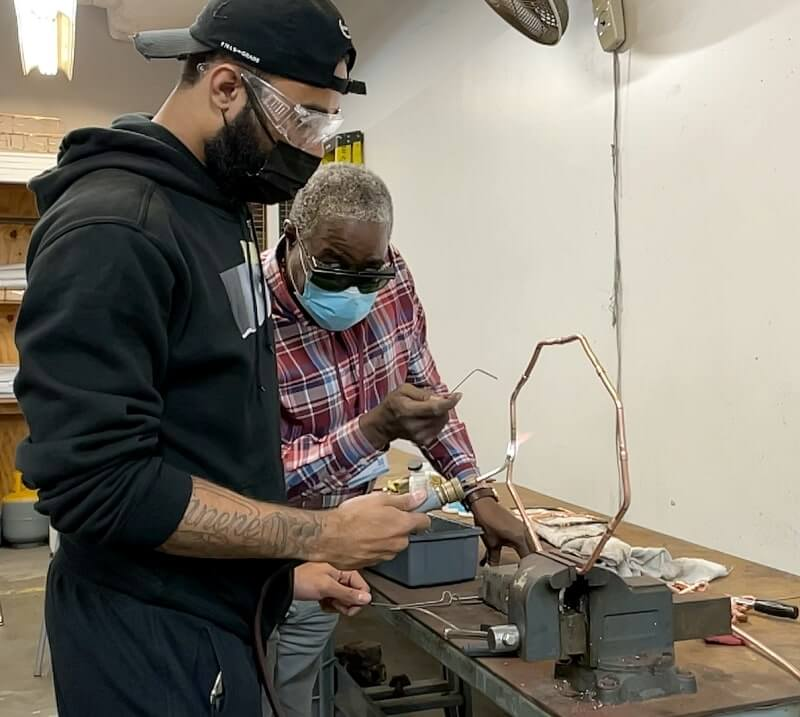 An Apex HVAC student and instructor work on wiring in the shop