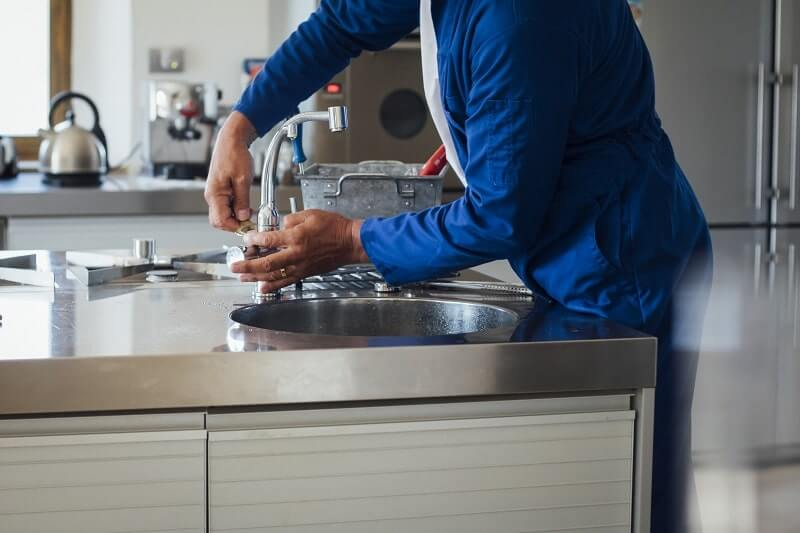 A residential plumber repairs a faucet on a kitchen sink