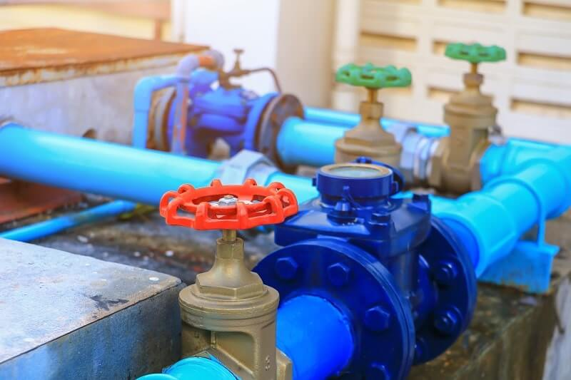 A red water valve on a blue commercial plumbing pipe