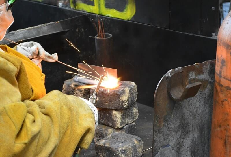 An Apex welding student learns to use a welding torch in the shop